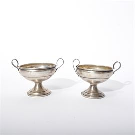 Pair of Sterling Silver Footed Urns: A pair of sterling silver footed urns. They are kantharos in shape, with round basins and two ear-shaped handles on either side. They sit upon round pedestals with subtle borders. They are cement weighted.