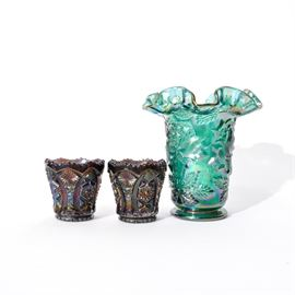 "Collection of Carnival Glass Vase and Cups: A collection of a carnival glass Fenton vase and two cups. The vase has a round foot with a subtly tapered vessel. The body is adorned with leaf motif. The mouth of the vase is ruffled. There are two cups in darker carnival glass by Imperial. They have a starburst and geometrical pattern with scalloped rims. The bottoms are marked with a ""G"" and a stylized ""I"". This mark was used by the company until 1972."