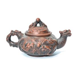 Chinese Yixing Ceramic Teapot: A Chinese Yixing clay teapot. The small teapot features a dragon's scaled neck and head as the spout. The vessel's body is adorned with stylized depictions of the beast's legs and talons. The ear shaped handle is comprised of another dragon head. The lid's handle is formed with two additional dragon heads, their mouths meeting to support a small globe finial. The pot has a burnt sienna patina over a black base. The bottom is marked with Chinese symbols within a square border.