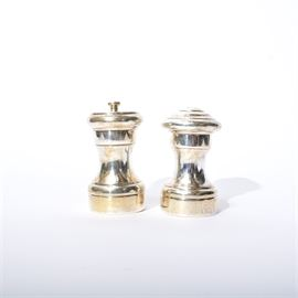 "Empire Sterling Silver Salt Shaker and Pepper Mill: A set of an Empire sterling silver salt shaker and pepper mill. They have round bodies tapering at the top and bottom with smooth borders. They are marked ""Empire Sterling"" and are weighted. They were made in Italy."