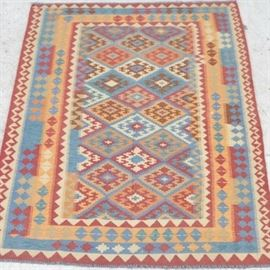 Turkish Kilims Rug: A handwoven Turkish kilim runner. This runner features a varying geometrical rhombus pattern in a palette of pale yellow, blue, olive green and red hues atop a corresponding pattern of matching colors. The runner has a compound border of small alternating medallions, waves and triangular designs The rug is complete with natural warp fringe to either end.