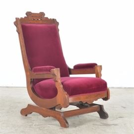 Eastlake Easy Chair: An antique Eastlake Easy Chair. The walnut straight back chair has a crown that is decoration with incised and carved accents. The S-shaped chair rests on a slight angle on springs and is supported by an H-shaped base. The chair is covered in mauve colored material.