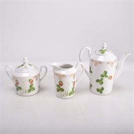 Antique German Porcelain Strawberry Coffee Set: An antique German porcelain coffee set. Decorated with an alpine strawberry pattern with gold accents along the shoulders, spouts, and handles. This set includes coffee pot, a cream pitcher, and a sugar bowl. Each piece is marked with an export mark for Beyer and Bock on the bottom. This mark was used by Beyer and Bock exclusively for the United States export market between 1905 and 1918.