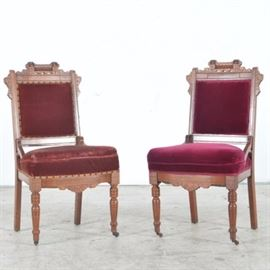 Antique Eastlake Side Chairs: A pair of antique Eastlake side chairs. The chairs have a walnut framed with a square chair rail. They are accented with incised decoration and rest on four turned legs with casters. One chair is covered in a mauve velveteen material, and the other is covered in red mohair.