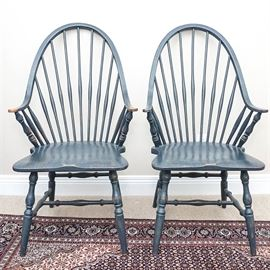Pair of Blue Windsor Style Dining Chairs: A pair of blue Windsor style dining chairs. Both of these chairs have fanned post backs with angled armrests. Both of these chairs rest upon two tapered legs in the back and baluster legs in fronts with spreaders between. Also included are four blue and white accent pillows.