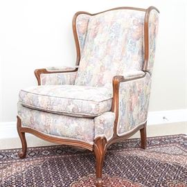 Burris Reclining Wingback Armchair: A Burris reclining wingback armchair. This chair has a square-patterned upholstery with each square containing a floral themed depiction. These are wooden accents along the wings, the reclining bottom edge, and both armrests. The chair rests upon four cabriole legs.