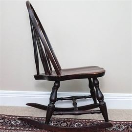 """Vintage Mahogany Brace Back Children's Rocking Chair: A vintage mahogany brace back children's rocking chair. This chair has a seven-reed back with two being pure vertical support. The chair has four baluster legs with spreads between that rest upon both curved rockers. Along the underside is a brand for """"Red""""."""