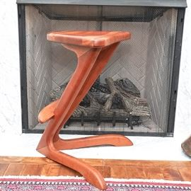 """2012 Handcrafted Pine Stool: A 2012 handcrafted pine stool. This stool has a triangular top with two angled support beams that rest upon barrister feet. There is a small foot rest along the middle of the beams, and along the underside is a marking of """"DH 2012""""."""