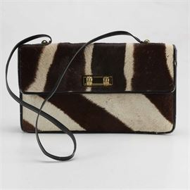 1950s Zebra Hide Handbag: A 1950s zebra hide handbag. This bag has a black leather base with the hide covering the exterior. There is a gold tone buckle along the front and brass fasteners for the shoulder strap. There is a bi-fold along the interior with a zipper along the divider.