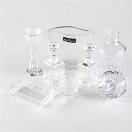 "Collection of Crystal Decanters and Decor: A collection of crystal decanters and home decor. Featured are three crystal decanters, one with palmette design and matching palmette drinking glass, as well as two smaller decanters with stoppers. One is marked ""Donegal Irish Crystal"" in a foil sticker to the front. The assortment also features a Marc Aurel crystal vase with etched giraffe pattern, a fluted bud vase, a rectangular crystal serving tray and a round crystal votive holder."