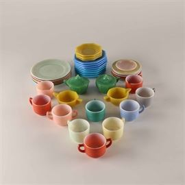 Agate Glass Tea Collection: An agate glass tea collection. This colorful lot includes twenty-four saucers of various shapes and sizes. Six cups, three sugar bowls, three creamers and two pieces with lids complete the set of thirty-eight.