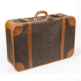 Vintage Louis Vuitton Suitcase: A vintage Louis Vuitton suitcase. This classic rectangular piece of luggage features the iconic monogram print coated canvas construction with brown leather trim and gold-tone hardware. It offers a zipper closure, buckled leather straps, and a hinged leather handle. The interior is fully lined. Made under license by The French Company.