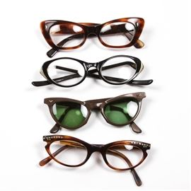 Collection of Vintage Glasses: A collection of vintage glasses. Featuring four pairs of eyeglasses. Three pairs have clear lenses and one pair is prescription sunglasses. All of the glasses have oval lenses and plastic frames.