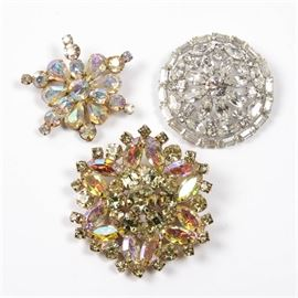 """Weiss Vintage Rhinestone Brooches: A collection of Weiss vintage rhinestone brooches. Featuring three pin-on brooches in different designs with colorful and clear rhinestones. All three brooches are marked """"Weiss""""."""