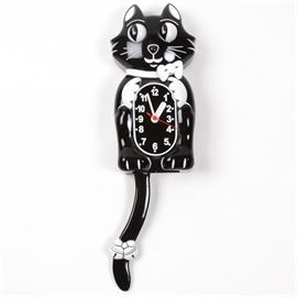 """Vintage Cat Clock: A vintage cat clock. Featuring a wall hanging clock in the shape of a black cat with a white bow on his neck and bandage on his tail. The eyes move in sync with the swinging tail pendulum. There are two white hour and minute hands and a red second hand. The clock is marked on the back """"Made in China""""."""