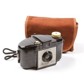 """Kodak Brownie 127 Camera: A Kodak Brownie 127 camera. Featuring a vintage hand held film camera with a cloth storage case with a shoulder strap and a snap flap closure. The vintage camera is marked on the face """"Kodak Brownie 127 Camera"""" and on the bottom """"Made in England by Kodak Limited London""""."""