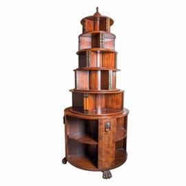 Hemingway Style Round Spinning Bookcase: A Hemingway style round spinning bookcase. This bookcase is comprised of stacking shelves. Each shelf has a rounded design and is slightly smaller than the one below it. At the top is a pointed finial while the bottom showcases carved, claw feet. The wood is a cedar stain with decorative geometric lines around the edges. In addition, the upper shelves have built in, decorative books. There are six stacked shelves in total. This item comes apart for moving and storage. It is connected by a center rod.