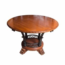 Hardwood Dining Table: A hardwood dining table. This dining table has a wooden table surface and base with an iron support frame. The table surface edges and feet have a carved design. The iron support frame has a circular motif and design. There are no makers marks on this table.