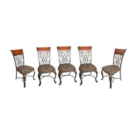 Set of Five Dining Chairs: A set of five dining chairs. This set of chairs have an iron frame, upholstered seat, and wooden seat back. The iron frame has curved legs and claw feat. The seat backs have carved wood at the top. Each seat is upholstered in a floral fabric. There are five chairs in this set.