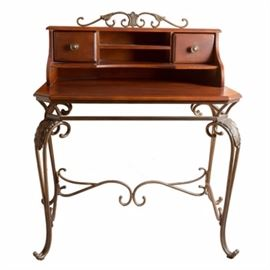 Wooden Secretary Desk: A wooden secretary desk. This desk consists of a wooden writing and storage section atop an iron base. The upper section has a squared writing surface with three slots and two drawers to the rear. Each drawer has a brass toned, round pull. The base is made of a silver toned iron. The legs have a carved leaf design. At the top, there is a matching iron decor piece. Each leg has a clawed foot with a curved, decorative center support. There is a faint serial number marking on the underside of the iron. The wood has a chestnut toned stain.
