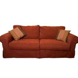 Upholstered Sleeper Sofa: An upholstered sleeper sofa. This sleeper sofa is upholstered in a brick red fabric. Included are two matching throw pillows. Under the seat cushions is a pull out bed. The bed has a metal frame and mesh support material. Please note, that the mattress is not included. The serial number of this sleeper sofa is S303158065. The fabric is made of polyester and rayon.