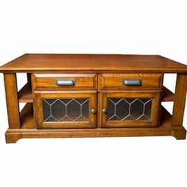 Hardwood Coffee Table: A hardwood coffee table. This coffee table is made of a medium stained wood. It has shelving on either side and small cupboards on the opposite sides. At the top, there are false drawers. The very top surface of the coffee table raises. Each door on the lower cupboards has a glass panel. This coffee table is accented with bronze toned, metal hardware.