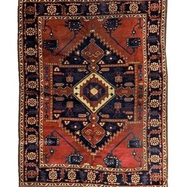 Hand Knotted Persian Area Rug: A hand knotted Persian area rug. This hand knotted area rug is made of woolen fibers and features a red field with cream, blue and red medallion, geometric shapes, blue inner border with floral motif and cream, blue and red inner and outer border with abstract pattern.