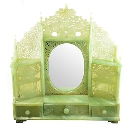Carved Serpentine Vanity with Mirror: A carved serpentine stone vanity with mirror. This unmarked rectangular jadeite hued serpentine stone vanity features an ornate Asian motif pierced top, a central oval mirror, carved side panels with pagoda motif with small triangular shelves, small work surface and three small drawers with raised Chinese characters on the fronts with round pulls.