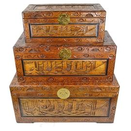 Ornately Carved Nesting Trunks: A trio of nesting trunks. These intricately carved pieces are made of light stained wood, carved with Asian style designs depicting boats sailing on scrolling waves, bordered by repeating flowers. They have gold tone latch closures, and the largest has detachable feet.
