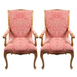 EJ Victor Louis XV Dining Chairs: A pair of EJ Victor upholstered Louis XV dining chairs. The chairs have a light oak wood frame with a floral carvings to the rails and skirts. Each chair is upholstered with a light red upholstery to the seat, back and arms and rests on four cabriole legs.