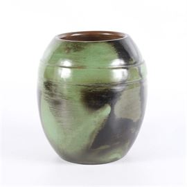 """Ernesto Ramirez Pottery Vase: A hand crafted pottery vase by noted artist, Ernesto Ramirez. The round piece is finished with an olive green and black painted finish and a band around the top. The piece is signed """"Ernesto Ramirez Chulucanas Peru"""" to the base."""