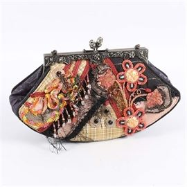 """Mary Frances Handbag: A hand crafted Mary Frances handbag. The hard-shell bag has an elaborately decorated exterior with beaded floral elements and fringe. The bag has a pink covered back a hard clasp to the top and is finished with a beaded chain strap. The interior is marked """"Mary Frances"""" and comes with a Mary Frances marked tag."""