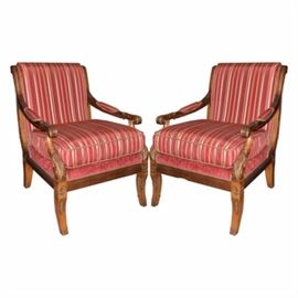 Pair of Upholstered Armchairs in Carved Wood Frames: A pair of upholstered armchairs with lovely carved wood frames. Chairs are upholstered in a burgundy, gold tone and sage striped sateen fabric. Arms are lightly padded in a matching fabric over carved wood. The back of the chairs and seating area below the cushions are upholstered in a deep orange chenille fabric. The front and sides of the wood frames are carved in a scroll and acanthus leaf pattern. Chair feet are gently curved.