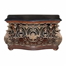 Rocco Revival Style Console Table: A Rocco Revival Style console table with a deep gray granite type surface. Surface is gently curved and beveled around the edges. The body is presented in a gold tone brushed finish and ornately decorated in acanthus leaves with scrolling details to the front and sides. This beautiful pieces sits atop a beveled wood base with carved beaded rope and bun feet. The back of this piece is open.