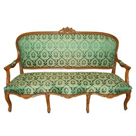 Louis XV Style Canapé Sofa: A Louis XV style canapé. This sofa features a wood frame with hand carved details and four legs to the front. Upholstered in a green and gold brocade fabric with brass nailhead trim.