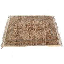 Accent Rug: An accent rug. A machine woven rug with a geometric central medallion in shades of cream, brown, dark brown, and black. With a cream fringe and machine bound edges.