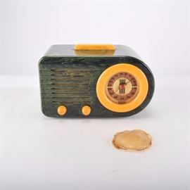 Vintage FADA Bakelite Radio: A vintage FADA 115 'Bullet' Catalin radio in a Bakelite case. The case is a marbled green with yellow accent handle, knobs and face edging. One side is straight and the other is rounded in an Art Deco design.