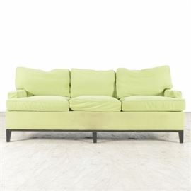 Chartreuse Color Upholstered Sofa: An upholstered sofa in a soft canvas chartreuse color. There are three back and three seat cushions, all removable. The sofa sits on black tapered wood legs.