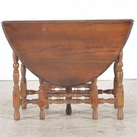 Walnut Top Gate Leg Table: A walnut top gate leg table, supported by nine turned legs. One of the legs is placed centrally with six side legs and two hinged legs that open to support the drop leaves. When opened, the table is oval. The table has cross spindles that support the legs.