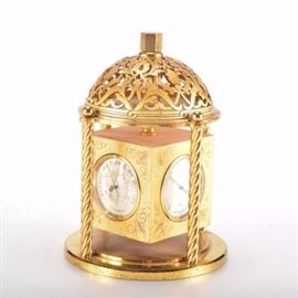 """Angelus Hygro Barometer: An Angelus clock/barometer. The etched brass cube contains a Swiss movement clock with Arabic numerals; a Hygro hygrometer; a Celcius dial thermometer and a barometer. The cube rotates underneath a curved, cut-out canopy flanked by rope columns. The piece is marked """"Angelus, Fifteen 15 Jewels"""" to the bottom."""