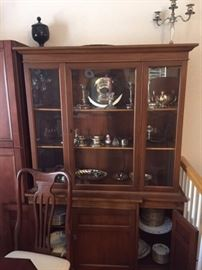 China hutch with china sets inside, plus silver and silver-plate dishes and serving pieces.