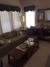 Large sofa, long coffee table, pillows, lamps, large gold mirror, large horizontal cabinet, decorative tables, electronics