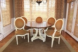 Round Pedestal Dining Table With Five Chairs: A French Country dining table with pedestal base and five French country dining chairs. The table features a distressed plank top finished in a medium stain. It is supported by a hand-painted pedestal base featuring curved legs, a low x-stretcher, and bun feet. This listing also includes two armchairs and three side chairs. Each features wooden frames constructed with balloon backs, curved seat rails, and square tapered legs. They are finished in a distressed hand-applied antique white and upholstered in a rich brown chenille with antiqued brass head trim. The armchairs feature padded manchettes.