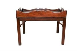 Antique Butler's Tray Coffee Table: An antique butler's tray coffee table. This walnut table features scalloped asymmetrical side rails, pierced hand-holds, and decorative corbel trim. It is raised on square legs with fluted detail to the inner edge.