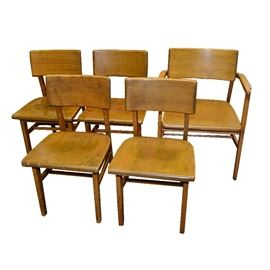 "Mid Century Remington Rand Birch Chairs: A collection of mid century Remington Rand birch chairs. The collection includes one armchair and four side chairs made of birch wood with a natural finish.Other features include a curved rectangular shaped wood back and square wood seat, a box style stretcher with three wood dowels in the center and the armchair has wood arms with an asymmetrical shape. The armchair is marked on the underside ""Remington Rand, Herkimer, NY""."