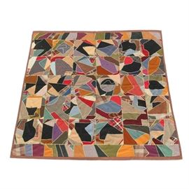 Semi-Antique Hand Embroidered Crazy Quilt: A semi-antique hand embroidered crazy quilt. This machine stitched item features squares of patchwork shapes in a variety of colors and patterns. On two opposing sides a rectangular panel sets off these squares. A thin solid color border surrounds the piecework, and this same color is used for the backing. The stitchwork thread is white and light green. The work is not marked with a maker's name.