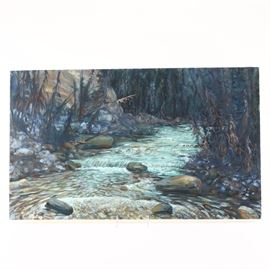"Robert Stagg Oil on Canvas ""Vermont"": An original oil painting on canvas titled Vermont by contemporary Kentucky artist Robert Stagg. This landscape piece features a central blue stream running over a series of multi-colored pebbles and stones of the river bed flowing between a series of small trees and bushes. Verso features artist name and piece title."