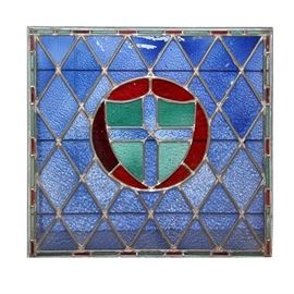 Stained Glass Panel With a Knights Cross Shield: A stained glass panel. The center features a blue cross on a green shield within a red circle. It is surrounded by a blue diamond pane square, framed with a red and green striped band. The panes and panels of glass are held with a silver tone leading. No discernible signature or maker's mark could be found.