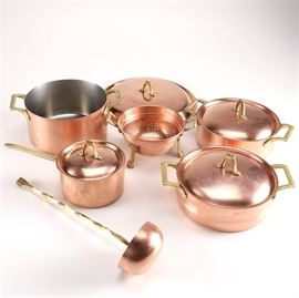 Paul Revere Copper Cookware: A selection of Paul Revere copper cookware. This selection includes three cooking pots with lids, a pot without a lid, a large extra lid, a strainer, and a ladle. Each item is made of copper with brass tone handles.