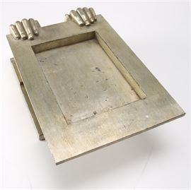 Metal Tray With Decorative Hands: A metal tray. This selection features a pair of metal hands holding a tray. It is comprised of brass tone metal and is set upon a stepped plinth.